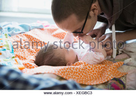 Father kissing hands of baby daughter on bed - Stock Photo
