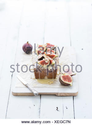Loaf cake with figs, almond and white chocolate on white serving board over white wooden background, selective focus - Stock Photo