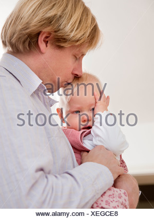 father comforting crying baby - Stock Photo
