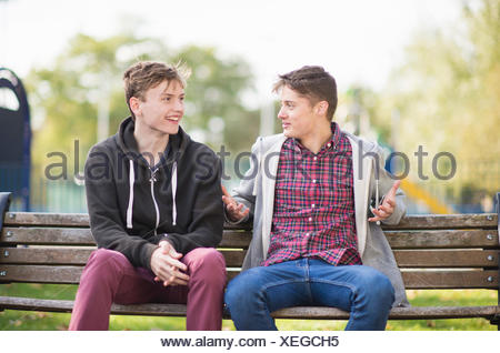 Two young male friends chatting on park bench - Stock Photo