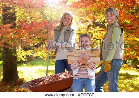 Three generation family doing yard work in autumn - Stock Photo