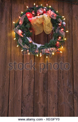 Christmas wreath with christmas lights on wooden door - Stock Photo