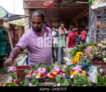 Ein Mann, die Blumen für pujas in der Nähe einen Tempel in Chandni Chowk, New Delhi, am späten Nachmittag. - Stockfoto