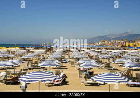 Hohen winkel Blick auf den Sandstrand von Lido di Camaiore mit Reihen von Sonnenschirmen an einem sonnigen Sommertag, Toskana, Versilia, Italien - Stockfoto