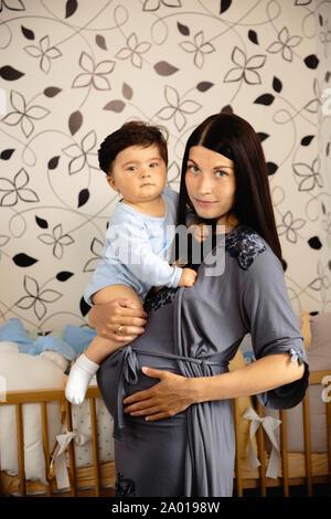 Schwangere Mutter Holding das Spielen mit ihrem Sohn mit ihm zu reden - Asiatische gemischte Ethnie Kind Junge trägt blaue Körper Shirt mit lächelnden Bär Cartoon - Stockfoto