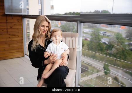 Junge blonde Mutter in Qualität, Zeit mit ihrem jungen Sohn am Haus der Familie flach - Mit Schwarzen budoir Kostüm Schlafrock - Stockfoto