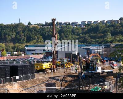 Ramme und anderen Bau Maschinen und Menschen arbeiten auf einer Baustelle in Huddersfield Yorkshire Engkand - Stockfoto