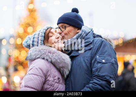 Gerne älteres Paar küssen am Weihnachtsmarkt - Stockfoto