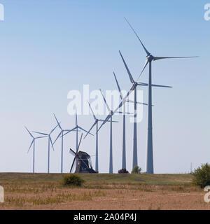 Alte holländische Windmühle und moderne Windenergieanlagen gegen den blauen Himmel in der niederländischen Provinz Groningen - Stockfoto