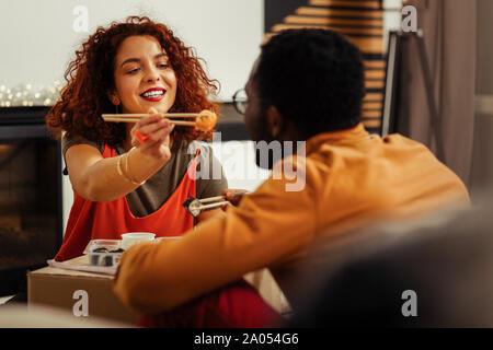 Es nehmen. Fröhliches Mädchen halten Lächeln auf Ihr Gesicht beim essen Sushi Rollen zusammen mit ihrem Partner - Stockfoto