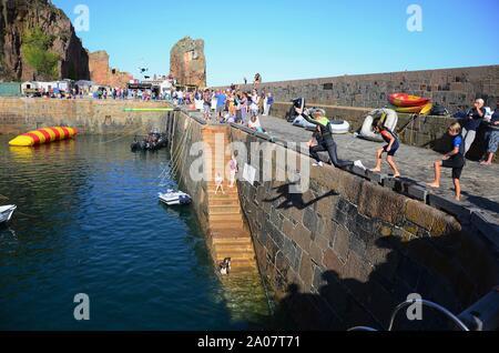 Kinder springen Kai in den Hafen von Build-A-Boat Spaß Tag am Creux Harbour, Sark, Kanalinseln. - Stockfoto