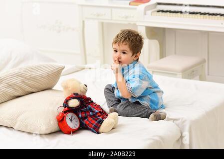 Kind im Schlafzimmer mit Stille Geste. Kid, Plüschbär in der Nähe von Kissen und Wecker, luxuriöse Innenausstattung Hintergrund. Zeit Konzept zu schlafen. Junge mit Ca - Stockfoto