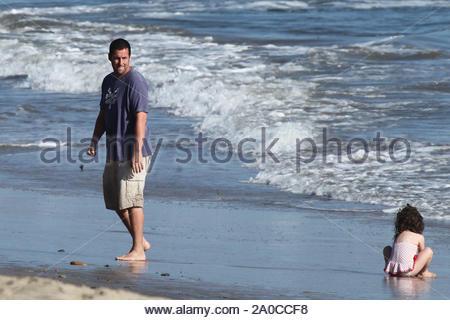 Malibu, CA - Adam Sandler spielt im Wasser mit Tochter Sadie, während Frau Jackie hält die jüngste Tochter Sunny in ihre Arme. Wenig sonnigen erhielt viel der Liebe von Mama und Papa, wie sie beide abwechselnd hielt an diesem Tag der Arbeit. Sadie gespielt Kissy mit Papa in die Arme wie die Sonne für den Abend ein. GSI Medien zum 7. September 2009 - Stockfoto