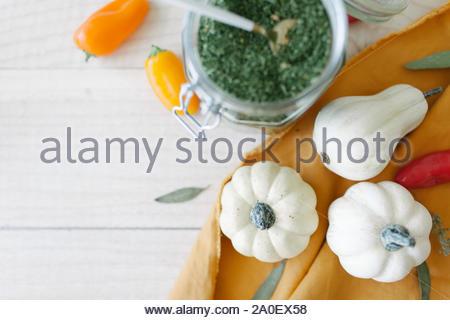Kleine creme Kürbisse, Mason jar Petersilie Flocken, Sweet Orange Paprika und Gewürzen mit Senf Serviette auf Ahorn Holz Hintergrund - Stockfoto