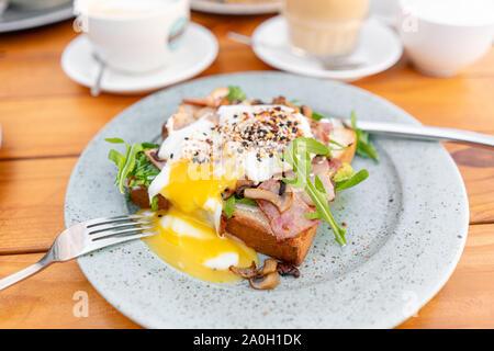 Frühstück und Kaffee im Sommer Cafe. Sandwich in einem Brötchen Brioche mit Speck, Champignons, Rucola und pochiertem Ei