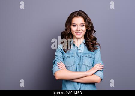 Schönes charmantes attraktiven fröhlichen herrliche adorable brunette kaukasische Mädchen mit gewelltes Haar in casual denim Shirt, verschränkte Arme, über Grau isoliert b - Stockfoto
