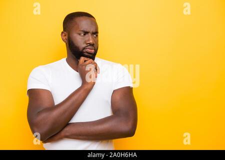 Schöne attraktive manly Sportliche mulato Kerl im weißen T-Shirt denken, Suchen, Kopieren - Raum, über hell leuchtend gelben Hintergrund isoliert - Stockfoto