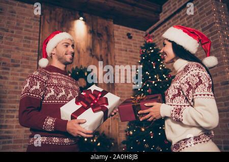 Low Angle View der Brünette Dame, stattlich attraktiver Mann in Ornament Pullover halten große Paket mit ausgefallenen Bug stand im Wohnzimmer Blick auf jedes andere m - Stockfoto