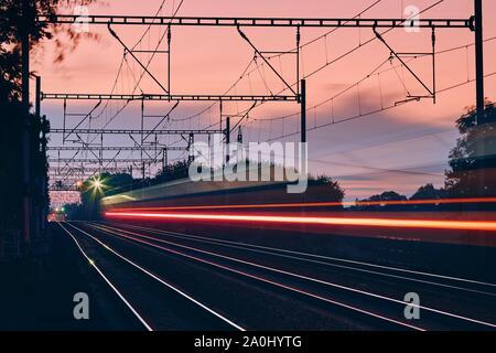 Eisenbahn in der Morgendämmerung. Leichte Spuren von Personenzug auf modernen Eisenbahn. - Stockfoto