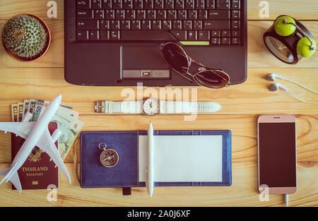 Draufsicht auf das Notizbuch, Stift, Sonnenbrille, Kaffeetasse, Pass, Geld, Handy, Ohrhörer, Armbanduhr, Kaktus, Uhr, Computer Maus und Kompass auf - Stockfoto