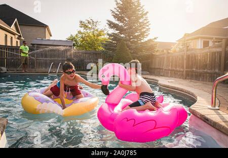 Zwei Jungen spielen in einem Pool auf aufblasbaren Pool Spielzeug. Stockfoto