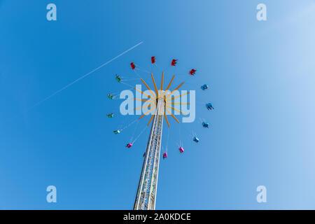High Flying Karussell gegen Straße blauer Himmel und Flugzeug Linie im Sommer auf einem großen Pol und 16 farbige Schemel in Blau Rot Grün und Pink eine schöne w - Stockfoto