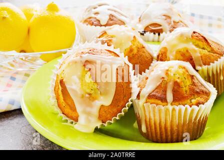 Hausgemachte Jumbo Größe Zitrone verglaste Mohn Muffins auf einem Lime Green Teller serviert. Frische ganze Zitronen werden im Hintergrund in einer Siehe durch Glas Bug - Stockfoto