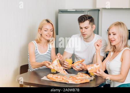 Drei kaukasischen gerne Studenten essen Pizza, trinken Orangensaft in der Küche. Freunde in Partei zu Hause, reden, lachen und Spaß haben. Freunde - Stockfoto