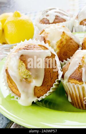 Hausgemachte Jumbo Größe Zitrone verglaste Mohn Muffins auf einem Lime Green Teller serviert. Frische ganze Zitronen sind im Hintergrund. - Stockfoto