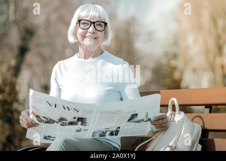 Strahlende elegante älteren Missis holding Papier im Park - Stockfoto