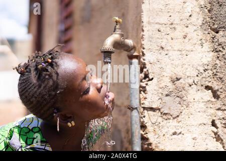 Gesunde, frische Wasser tropft von der Afrikanischen Kind Mund Tippen
