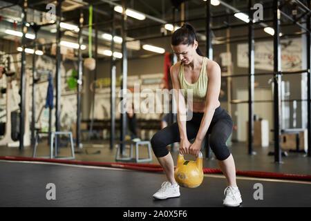 In voller Länge Porträt einer starken Frau heben kettlebell während Kreuz trainieren Sie im modernen Fitnessraum, Kopie Raum - Stockfoto
