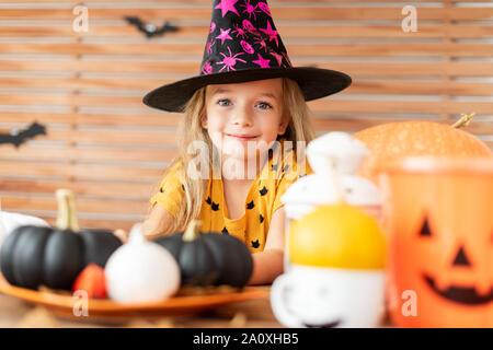Süße kleine Mädchen mit Hexenhut hinter einem Tisch mit Halloween Kürbisse sitzt. Mädchen in Halloween Kostüm auf Kamera, lächelnd. - Stockfoto