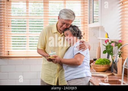 Asiatische älterer Mann überraschen ältere Frau mit Geburtstag Kuchen in der Küche zu Hause. umarmen und genießen die Zeit togethe, Altern zu Hause Konzept - Stockfoto