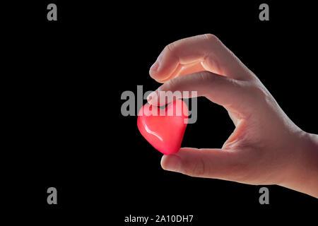 Isolierte Hand mit einem roten candy Form Herz auf einem schwarzen Hintergrund. - Stockfoto