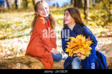 Zwei süße Lächeln 8 Jahre alte Mädchen in einem Park Plaudern auf einem sonnigen Herbsttag. - Stockfoto