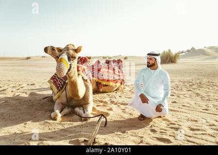 Mann, der traditionellen Kleidung, wobei ein Kamel in der Wüste Sand, in Dubai