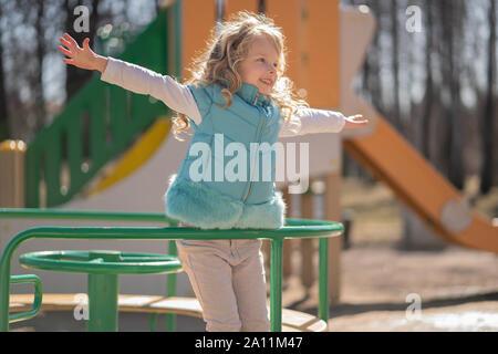 Cute curly blonde Mädchen in Blau aufgeblasen Weste freut und spielt auf dem Spielplatz im Stadtpark. - Stockfoto