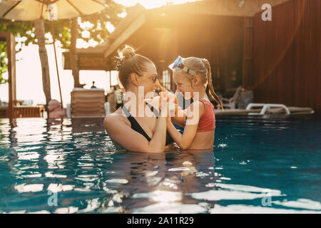 Lächelnde Mutter und ihre süßen kleinen Tochter stossen sich gegenseitig auf die Nase, während gemeinsam in einem Schwimmbad in ein tropisches Resort - Stockfoto
