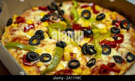 Eine Nahaufnahme einer Pizza mit schwarzen Oliven, goldene Mais, rote Paprika, grüne Paprika nachfüllen - Stockfoto