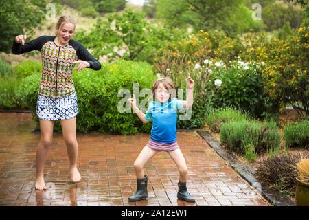 5 Jahre alten Jungen und seine 13 Jahre alte Schwester tanzen im Regen. - Stockfoto