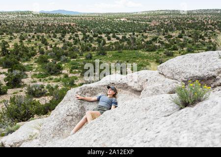 Der 13 Jahre alte Mädchen liegen auf Felsen, Tsankawi Ruinen, NM - Stockfoto