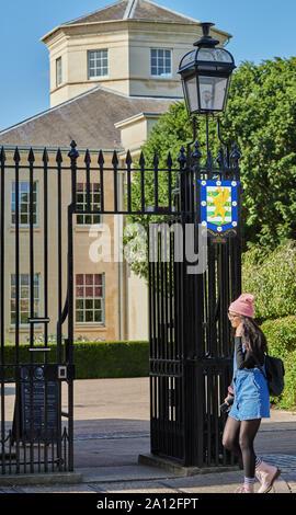Eine Studentin an der Emblem auf dem Tor am Haupteingang zur Downing College der Universität Cambridge, England. - Stockfoto