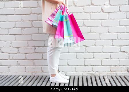 Shopping Konzept. Girl holding Bündel Tüten mit Käufen in der Nähe von Backstein Hintergrund. Kopieren Sie Platz. Sale, Discount, schwarzer Freitag Konzept. Shopping - Stockfoto