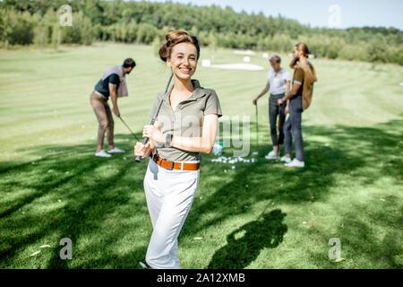 Porträt eines eleganten jungen Frau, die mit Golf Putter und Freunden Golf spielen auf dem Hintergrund - Stockfoto