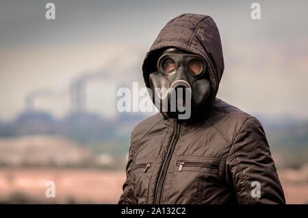Porträt eines Mannes in einer Gasmaske und einer Kapuze vor dem Hintergrund der Rauch von der Fabrik Leitungen dicht bis - Stockfoto