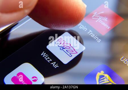 Wizz Air App auf dem Bildschirm und einen Finger über es zu wählen. Es ist von Ryinair, Virgin Trains umgeben Apps. - Stockfoto
