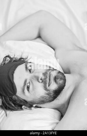 Man Gefühl Rückenschmerzen im Bett nach dem Schlafen. Faul Mann glücklich Aufwachen im Bett steigende Hände in den Morgen mit frischen Gefühl entspannt. Sleepy Kerl Aufwachen früh nach Anhörung Alarm Clock Signal am Montag morgen - Stockfoto