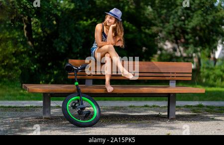 Junge Frau mit Einrad sitzen auf einer Parkbank Stockfoto