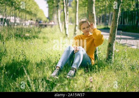 Porträt der nachdenkliche junge Frau sitzt auf einer Wiese im Abstand suchen Stockfoto